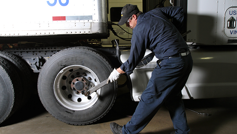 Driver Checking Truck's Tires